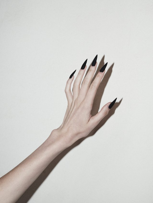 Colour image of a models hand with long nails